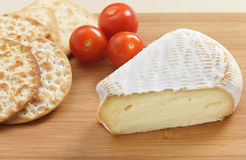 St Albray cheese. A wedge of St Albray cheese with crackers and cherry tomatoes on a cheeseboard Royalty Free Stock Photos