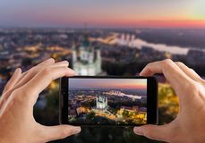 Travel concept. Hands making photo of St. Andrew`s Church Kiev Ukraine. Cityscape from a height. St. Andrew`s Church Kiev Ukraine. Cityscape from a height. City Stock Image