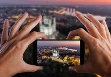 Travel concept. Hands making photo of St. Andrew`s Church Kiev Ukraine. Cityscape from a height. St. Andrew`s Church Kiev Ukraine. Cityscape from a height. City Royalty Free Stock Image