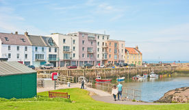 St Andrews harbor. Historic St Andrews harbor  with fishing boats berthed and fish houses converted to colorful modern apartments Royalty Free Stock Images