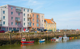 St Andrews harbor. Historic St Andrews harbor  with fishing boats berthed and fish houses converted to colorful modern apartments Stock Photo