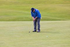 Man putting a ball at famous golf course StAndrews, Scotland stock photos