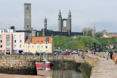 People walking at pier near harbor of Scottish St Andrews royalty free stock images