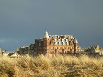 St Andrews Scotland. Sunlight shining on building overlooking the old course at St Andrews with grey sky of rainfall in the background royalty free stock photography