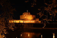 St Angelo Castle. In Rome, at night. Unique rounded fortress seen in golden light from the opposite bank of the river. Romantic scenery Royalty Free Stock Photos