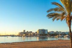 St Antoni de Portmany,  Ibiza,  Balearic Islands, Spain.  Calm water along boardwalk & beach in warm, late day sunlight. Royalty Free Stock Photos