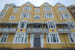 St Aubyns Mansions on Kings Esplanade, Hove, East Sussex, UK. Restored mustard coloured block of flats overlooking the sea royalty free stock images