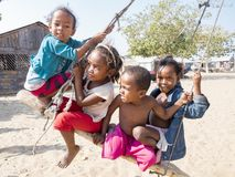 Local kids on swing in village royalty free stock photography