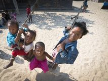 Local kids on swing in village royalty free stock photo