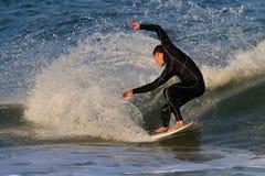 St Augustine, FL - 17 de febrero - persona que practica surf monta las ondas en la puesta del sol en el St Fotos de archivo