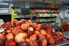 St AYGULF, VAR, ПРОВАНСАЛЬ, ФРАНЦИЯ, 26-ое августа 2016: Куча вкусных свежих персиков при клиенты покупая овощи в провансальском  стоковая фотография
