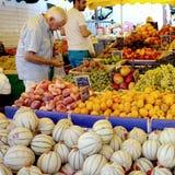 St AYGULF, VAR, de PROVENCE, FRANKRIJK, 26 AUGUSTUS 2016: Een klant die de kiwi, perziken, druiven, meloenen en ander fruit contr Royalty-vrije Stock Foto's