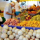 St AYGULF, VAR, PROVENCE, FRANCE, AUGUST 26 2016: A customer checking the kiwi, peaches, grapes, melons and other fruit on a Prove. Ncal market stall in France Royalty Free Stock Photos