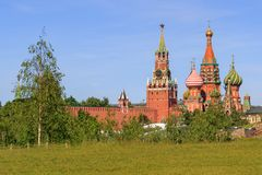 St. Basil`s Cathedral and Moscow Kremlin towers against green lawn on a sunny summer morning. View from Zaryadye Park royalty free stock images
