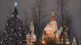 St. Basil`s Cathedral on Red Square against the backdrop of Christmas decorations and passers-by.