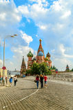 St. Basil`s Cathedral on Red Square and unidentified tourists walking along in Moscow, Russia. stock photo