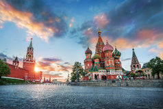 St. Basil`s Cathedral and Spasskaya Tower. St. Basil`s Cathedral and the Spasskaya Tower of the Moscow Kremlin and the summer sunset with colorful clouds royalty free stock image