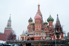 St Basil Temple and Spasskaya Tower of Kremlin during snowfall Stock Images