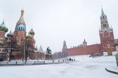 St Basil Temple and Spasskaya Tower of Kremlin during snowstorm. St Basil Temple and Spasskaya Tower of Kremlin at wintertime during snowstorm. The Red Square royalty free stock photography