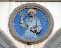 St. Bernardino of Siena, Ospedale di San Paolo in Florenece. St. Bernardino of Siena, glazed terracotta tondo by Andrea della Robbia, located between two arches stock photography