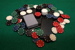 21st century - online casino. 21st century casino - online casino. Deck of cards, chip, and mobile phone on the tablet surrounded with different poker chips stock photo