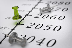 21st Century Timeline, year 2050. 21st Century timeline over paper background with green pushpin pointing the year 2050, blur effect, conceptual image stock illustration