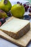 St?ck franz?sischer K?se Tomme de Brebis machte von der Schafmilch, die als Nachtisch mit frischen Feigen und Birnen gedient wurd stockfotografie