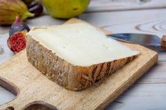 St?ck franz?sischer K?se Tomme de Brebis machte von der Schafmilch, die als Nachtisch mit frischen Feigen und Birnen gedient wurd stockfoto