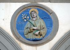 St. Clare, Ospedale di San Paolo in Florence. St. Clare, glazed terracotta tondo by Andrea della Robbia, located between two arches of the old Ospedale di San royalty free stock photography