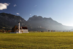 St. Coloman near Schwangau. The well-known church St. Coloman near Schwangau in Allgäu, Bavaria, Germany, with the famous Neuschwanstein Castle in the Royalty Free Stock Photography