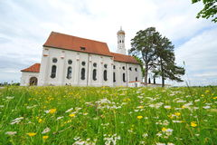 St Colomon church of Bavaria surrounded by spring flowers Stock Images