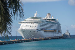 St. Croix--Royal Caribbean Cruise Ship Docked and People on Pier. Large commercial cruise ship is docked at pier in St. Croix as cruisers walk along pier to and Royalty Free Stock Image