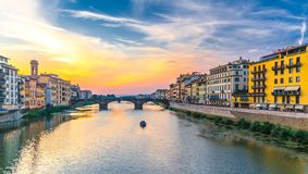 St de de de steenbrug en boot van de Drievuldigheidsbrug op het water en de dijk van Arno River wandelen langs met gebouwen in hi stock fotografie