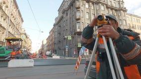 ST DELLA RUSSIA PETERBURG- 22 APRILE: l'ingegnere esamina la stazione totale nel centro urbano, su un fondo dei lavori stradali stock footage