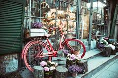 St?dtisches Fahrrad geparkt zu einem Blumenladen stockbilder