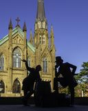 St. Dunstan`s Basilica Cathedral and the bronze statue of two Fathers of Confederation in the beautiful morning in Charlottetown royalty free stock image