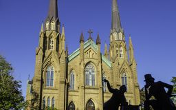 St. Dunstan`s Basilica Cathedral and the bronze statue of two Fathers of Confederation in the sunny day in Charlottetown stock images