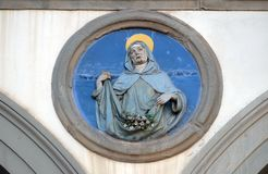St. Elizabeth, Ospedale di San Paolo in Florence. St. Elizabeth, glazed terracotta tondo by Andrea della Robbia, located between two arches of the old Ospedale royalty free stock photos