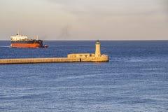 St Elmo Breakwater Lighthouse com um navio e os rebocadores de recipiente, no porto grande, Malta fotos de stock royalty free