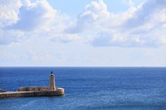St. Elmo`s lighthouse at Valletta, Malta. Breakwater of grand harbor between blue sea and sky background. Royalty Free Stock Photo