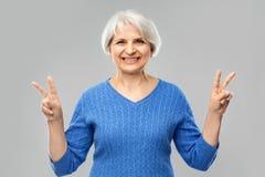 St?ende av att le den h?ga kvinnan som visar fred royaltyfri fotografi