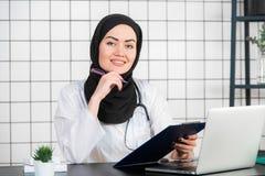 St?ende av att le den muslimska kvinnliga doktorn p? hennes kontor royaltyfri bild