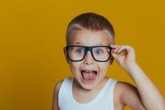 St?ende av den attraktiva pojken i den vita t-skjortan och svarta exponeringsglas p? gul bakgrund royaltyfria foton