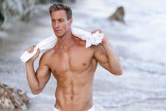 St?ende av den brunbr?nda f?rdiga manliga modellen med en naken torso p? stranden fotografering för bildbyråer