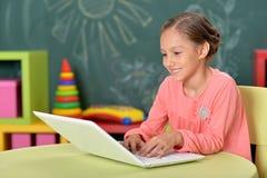 St?ende av den emotionella lilla flickan som anv?nder b?rbara datorn, medan sitta p? skrivbordet i klassrum royaltyfri foto