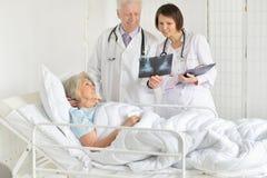 St?ende av den h?ga kvinnan i sjukhus med att att bry sig doktorer royaltyfri foto