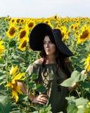 St?ende av den h?rliga flickan med solrosor H?rlig s?t flicka i kl?nning och hatt som g?r p? ett f?lt av solrosor som ler royaltyfria bilder