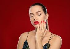 St?ende av den h?rliga unga kvinnan med ljus manikyr Spika polska trender arkivfoton