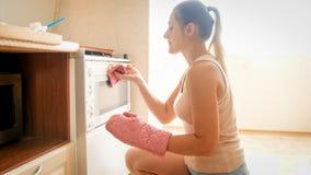 St?ende av den h?rliga unga kvinnan som s?tter bakningpannan med kakor i den varma ugnen p? k?k arkivbilder