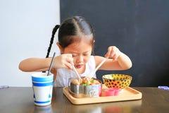 St?ende av den lilla asiatiska barnflickan som har frukosten p? morgonen arkivfoto